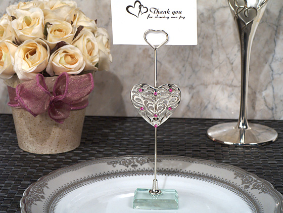 each silver place card holder has an ornate silver heart design accented with pink crystals it is attached to a metal stick holder